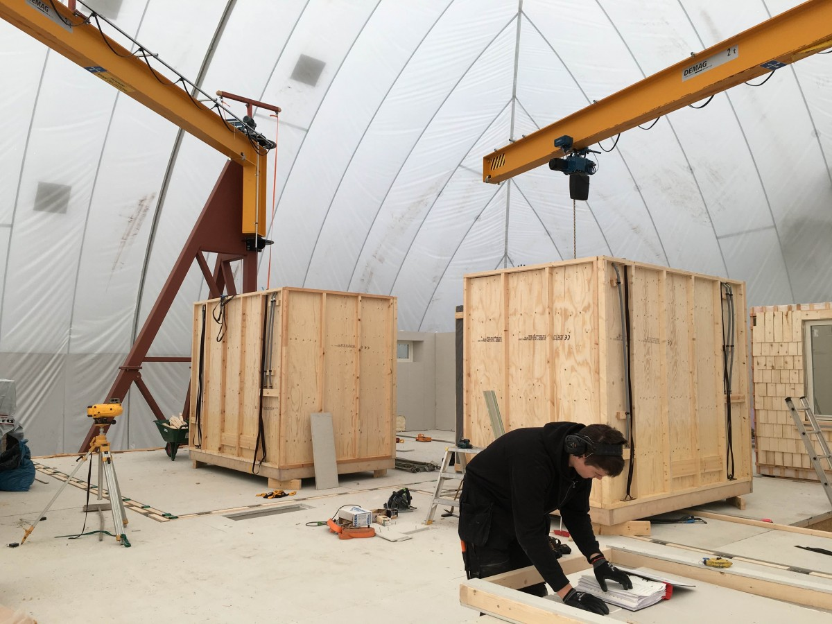 Bygge inuti väderskyddande tält med lyftkranar som når överallt.