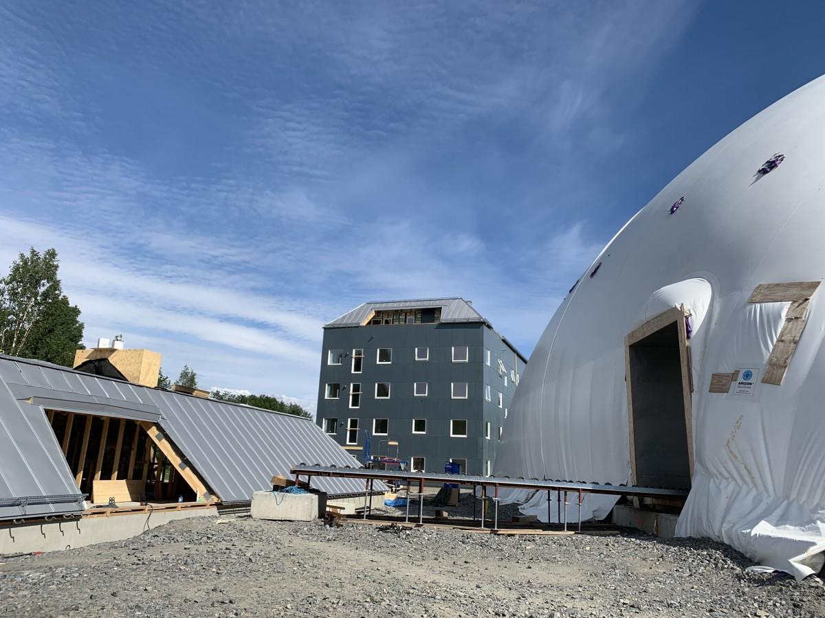 Till vänster taklägenhet på marken i väntan på lyft. Till höger tält som väderskydd.