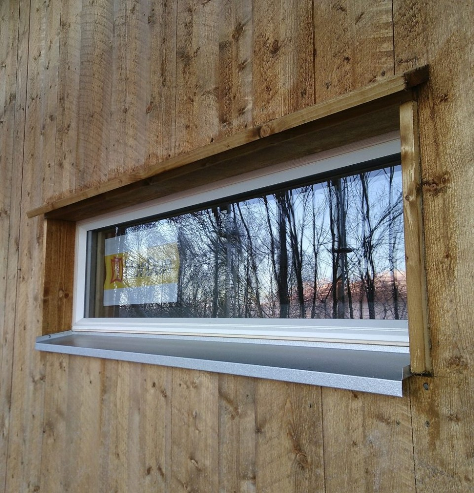 Långsmalt fönster med droppnäsa av trä och aluzinkbleck.