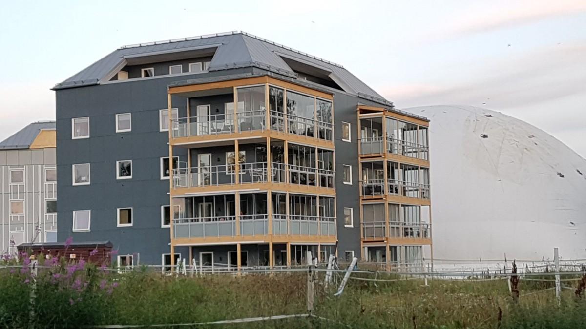 Hus nummer ett under byggnation. Inglasade träbalkonger.